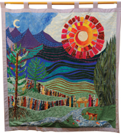 A colorful quilt with a sun, crescent moon, clouds, mountains and a forest-like background.