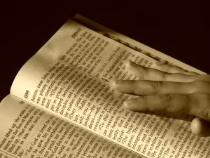 sepia tones, bible in forground and left, right hand holding it stretched across the right handed page