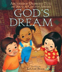 the front cover of God's Dream by Desmond Tutu. With a background of various textiles in many colors and patterns, a trio of children hold hands and look up into the center of the image.  The children are from different cultures, one white boy with brown hair, one black girl with pigtails, and one Asian girl.
