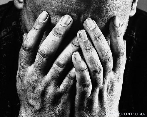 A person with head bowed into open hands in a gesture of grief