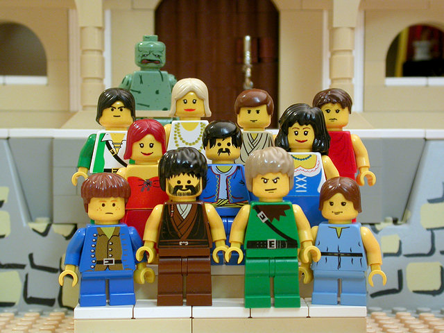 In an image from the Brick Testament, a webpage with Bible stories enacted in Lego toys.  This image is of Job 42:13 the restoration of job's family with 7 sons and 3 daughters.  They are standing, arranged on the steps of a grand house, in rows, facing the imagined camera. Job is still afflicted by the skin disease and appears green and scaly (in the upper left).