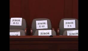 Against a wood panelled wall, the photo shows six chairs marked with labels for juror numbers.  The Jury in question is that of the Zimmerman trial in Sanford, FL.