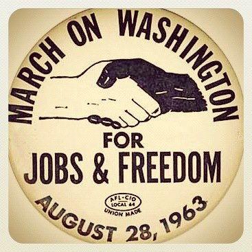 "A button for the event on August 28, 1963, ""The March on Washington for Jobs and Freedom"", shows and image of clasped hands one white and the other black."