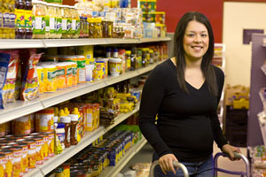 Patty stands in a grocery aisle.  She is wearing black and has a walker.  She is looking directly into the camera with a broad smile.