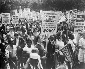 "black and white crowd photo during the March on Washington.  People are holding signs of ecumenical unity.  In the foreground is one that says, ""We march together, Catholic, Jews, Protestants, for dignity and brotherhood of all men under God Now!"