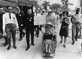 "A crowd marches - prominantly in the center of the photo is an older woman in a wheelchair holding a sign which reads, ""Synod of Virginia, Presbyterian Church US."""