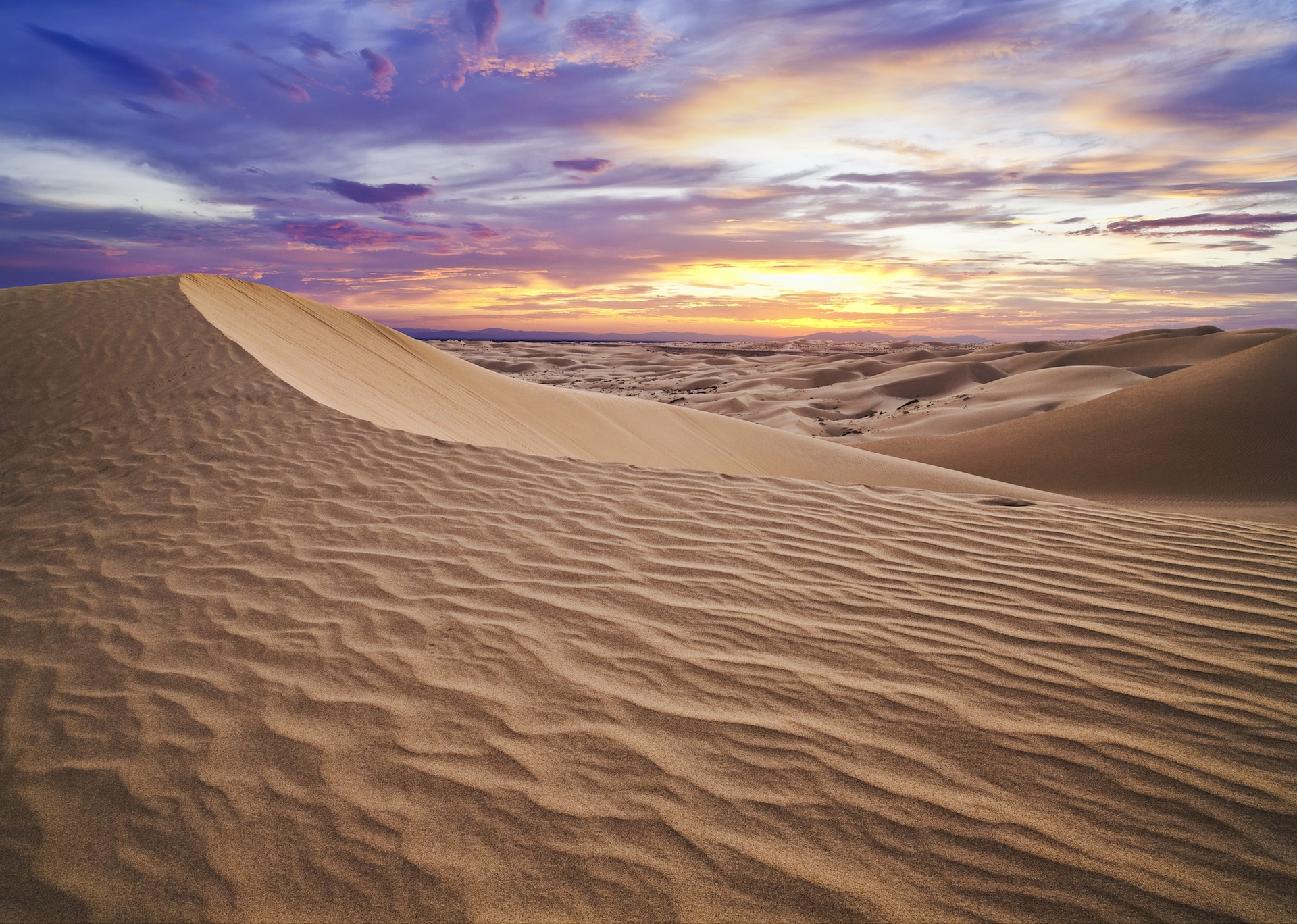 desert sand dunes at sunrise, the sky filled with light clouds and mixture of purple, blue and pink hues.