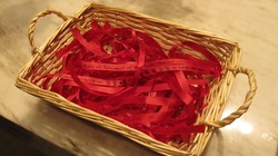 Red ribbons with writing on them in a basket