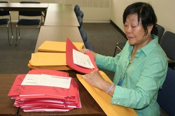 Peng Leong stuffing envelopes with Red Hands