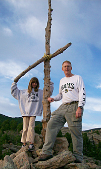 Man and young girl outside, standing next to a wooden cross
