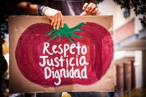 sign with a tomato reading respeto justicia dignidad