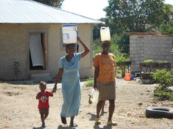 Women carry water from a solar powered water pump to their homes in the eco-village