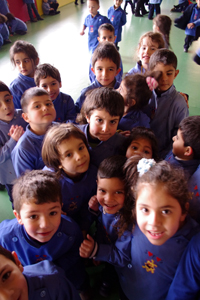 Schoolchildren in front of a camera, smiling.
