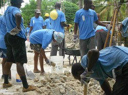 Haitian workers clear rubble near Léogâne