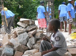 A young boy watches a Haitian work crew clear rubble