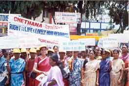 Women demonstraing and holding up Chethana signs.