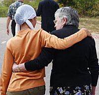 Two women walk with their arms around each other