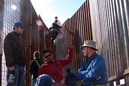 Photo of six men standing in bright sunlight next to two tall walls.