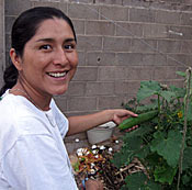 Photo of Miriam Adams standing next to a zucchini plant. She is smiling. In the background is a cinderblock wall.