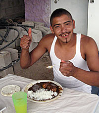 Photo of a young man in a sleeveless white shirt sitting at a  table with spoon in hand. He is looking at the camera, smiling, and  giving the #thumbs up