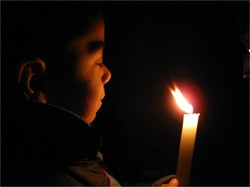 Photo of a boy with eyes closed, holding a candel which illuminates his face.