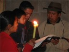 Photo of two men and a woman. The woman holds a candle. One of the men holds a child and reads from a book.