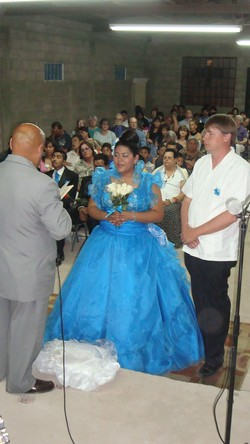 Photo of Cindy in a blue dress; Mark stands to her left; a crowd of people is sitting behind them.