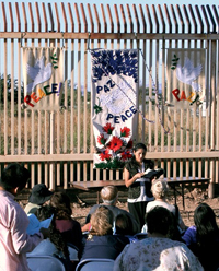 "A woman speaks to a crowd outside, in front of a tall fense decorated with handpainted cloth signs that say ""peace"" and ""paz""."