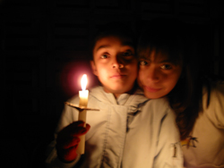 Two children together in the dark as one holds a candle.