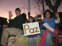 "A group of people on a float, with a sign that says, ""Paz""."