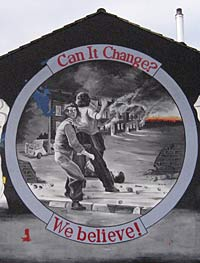 "Photo of a mural painted on a wall that says ""Can It Change? We Believe."" The image shows several youths throwing stones on a street where houses are going up in smoke."