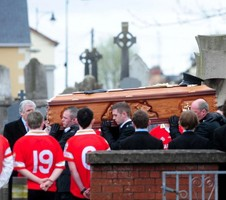 PHoto of men with a coffin on their shoulders. Some onlookers are wearing sports jerseys.