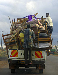 Photo of a small pickup truck loaded with furniture. Two men are hanging on to the load, which is piled very high.