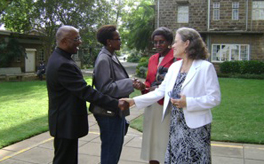 Photo of Marta Bennett shaking hands with a man. Behind them are two women greeting.