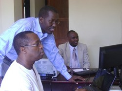 Photo of three men looking at a computer monitor.