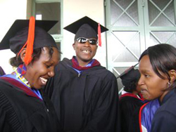 Three graduates standing together, smiling.