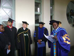 A group of graduates standing together, with someone reading a document.