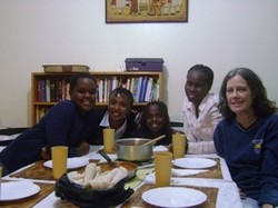 Photo of Marta and children at dinner table.