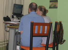 Photo of a man and woman looking at something on a laptop screen.