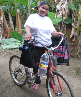 Photo of a girl standing next to a bicycle. She is holding bags, water bottles hang from the handle bars.