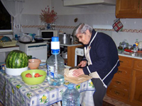 An older woman in a kitchen, slicing food.