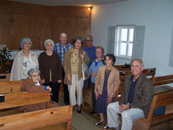 A group of people standing in a church, in between rows of pews.