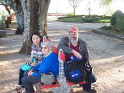 Three people sitting on a red bench outside near a tree.