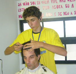 A young man cuts another man's hair