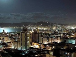Photograph of a city at night. The moon is reflecting off water at the city's edge.