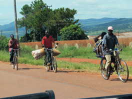 Photo of three people on bicycles with various packages and bundles.