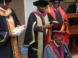 Photo of a man, who is kneeling; another man stands behind him and puts an academic hood him.