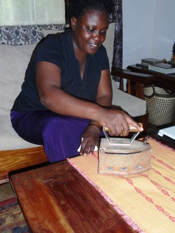 Photo of a woman ironing with an iron that has a very deep container above the ironing surface.