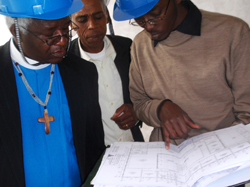 Three men review a construction plan.