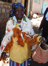 A woman in traditional dress, holding a hand-made basket.